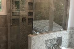Custom frameless Skyline shower sliding door with return panel brushed stainless hardware and clear tempered glass